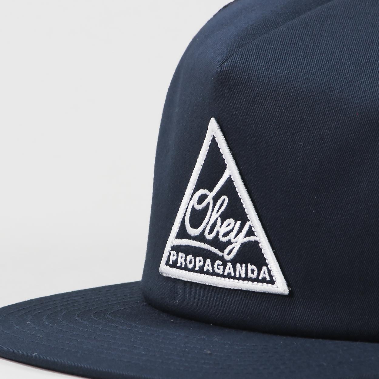 75dc5711938 A trucker hat from streetwear giants Obey featuring fully mesh back  paneling and a white embroidered  Propaganda  logo on the front.
