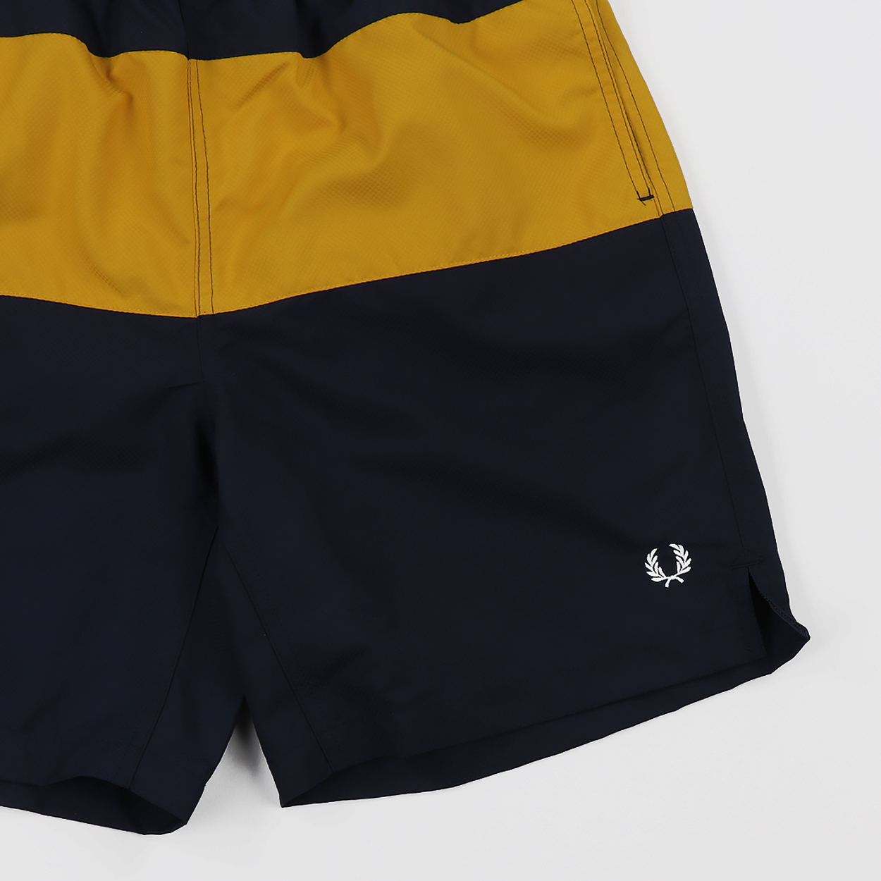 6a9cc218bd A pair of swimming shorts from Fred Perry made from 100% polyester with a  mesh lining. They feature a panelled colourblock pattern and an embroidered  logo ...